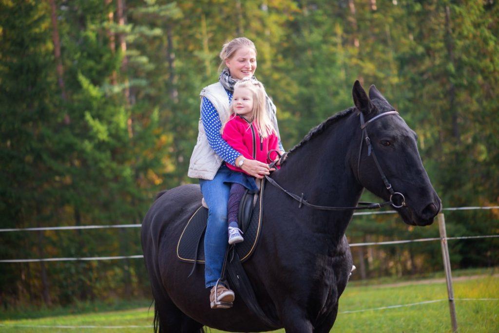Mutter und Tochter auf einem Pferd