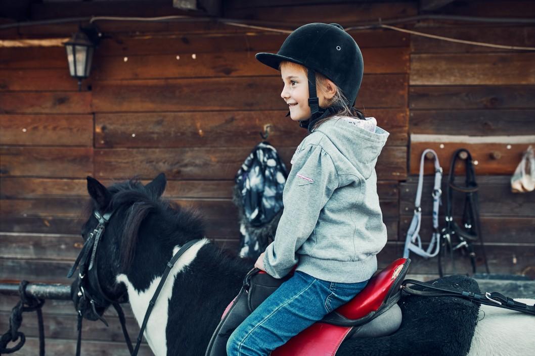 kleines Mädchen lernt reiten